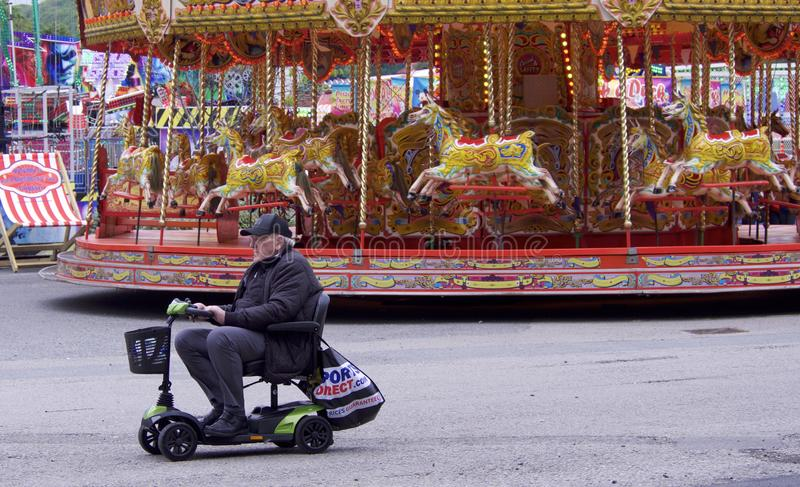 Bank Holiday Weekend Fairground ride and man on mobility scooter. Looe, Cornwall, 05.26.2019 Older white man on mobility scooter in front of fairground carousel stock image