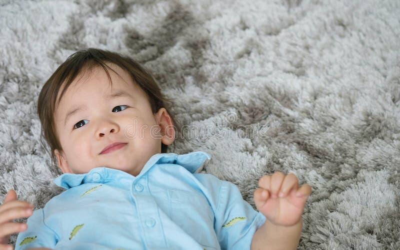 Loog het close-up leuke Aziatische jonge geitje op vloer in gelukkige emotie met glimlachgezicht op grijze tapijt geweven achterg royalty-vrije stock foto's