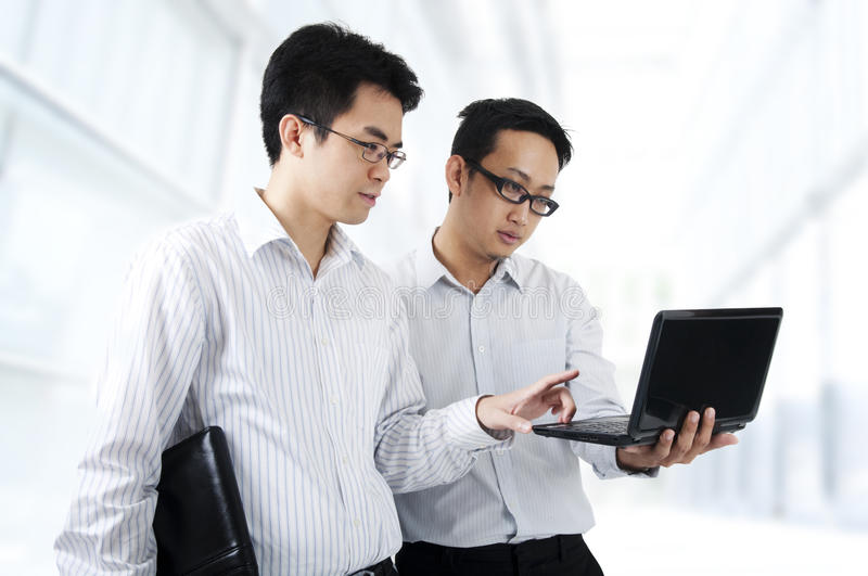 Look At This. Two Asian young executives working on laptop, office building as background stock photography