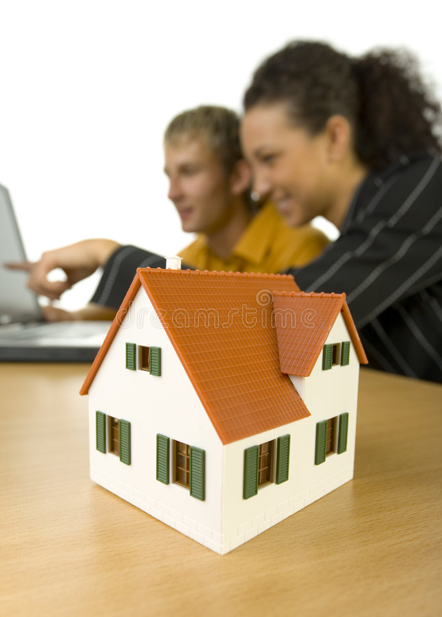 Look at that. Young couple sitting at desk in front of computer. Woman is showing something. House miniature is standing on desk. Focus on little house. White royalty free stock image
