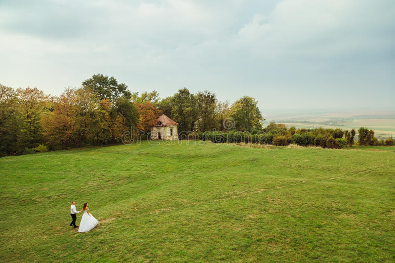 Look from above at comely wedding couple walking. Across the green field stock photos
