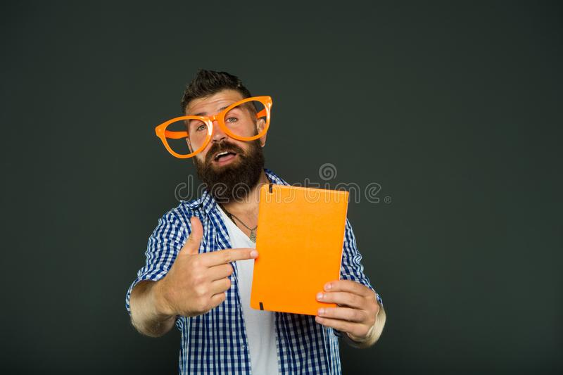Look at this book. Bearded man in party glasses pointing at lesson book. Study nerd holding book. Book nerd wearing stock photos
