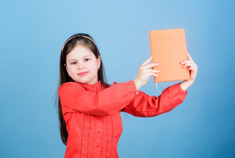 Look at this book. Small pupil took the book from library. Adorable school child with activity book. Cute little girl. Holding note book with orange cover, copy royalty free stock photography