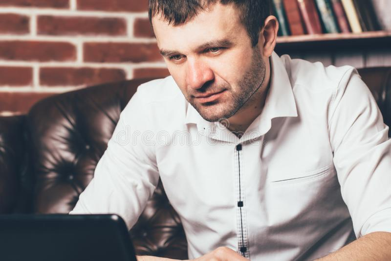 The look of a businessman is chained to the laptop. A man is absorbed in working on his business stock image