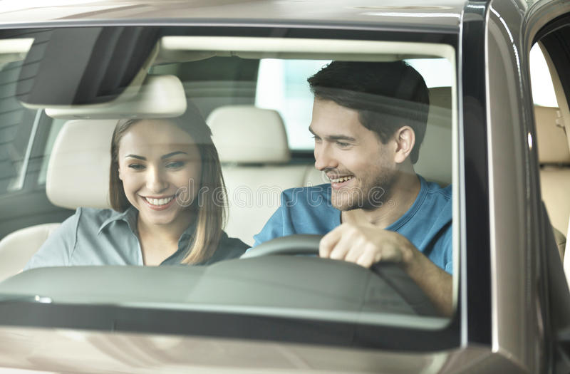 Look at this console! Beautiful young couple sitting at the front seat of the car checking out the side panel stock photos