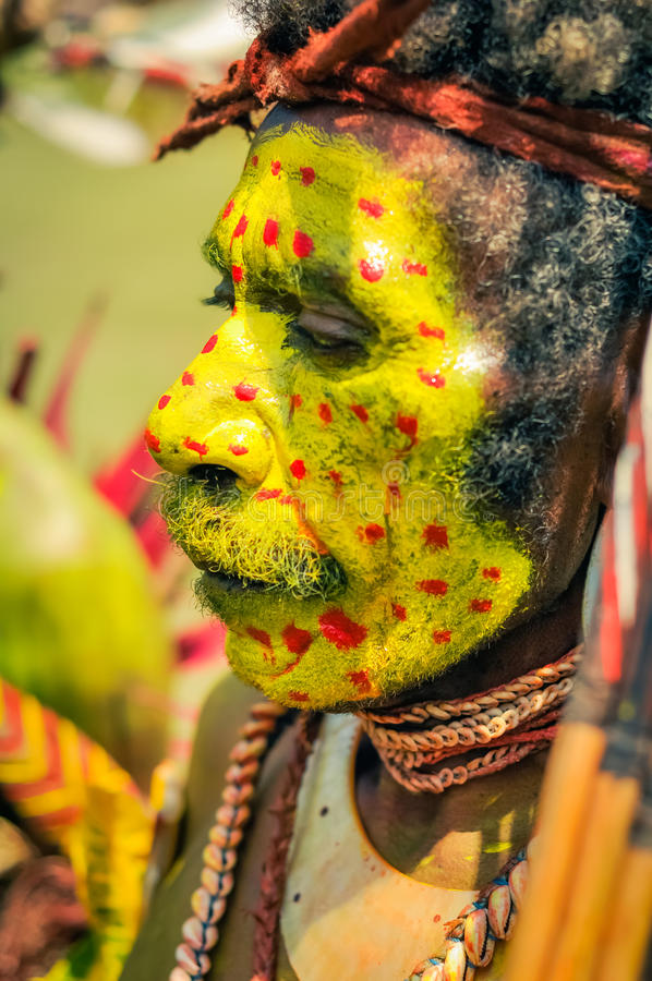 Look down in Papua New Guinea. Hagen show, Papua New Guinea - circa August 2015: Old native man with moustache and face covered in yellow colour with red dots royalty free stock image