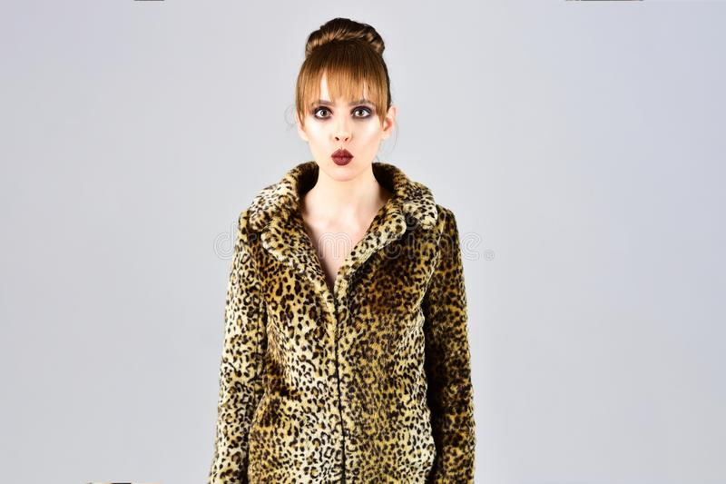 Look of fashion model with bad taste. Leopard fur at stylish girl. Woman in leopard fur coat on grey background. Fur stock photo