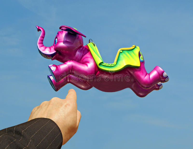 Look!flying pink elephant. Photo of an arm pointing to a pink elephant flying through the bright blue skies waiting to take someone on a magical mystery tour royalty free stock image