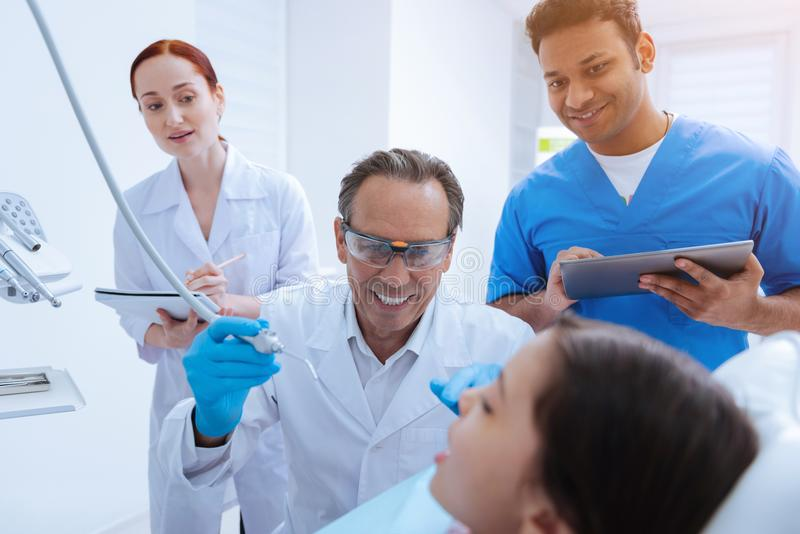 Scared girl looking at her doctor. Look forward. Joyful dentist keeping smile on his face and wearing protective glasses while going to treat bad teeth royalty free stock photography