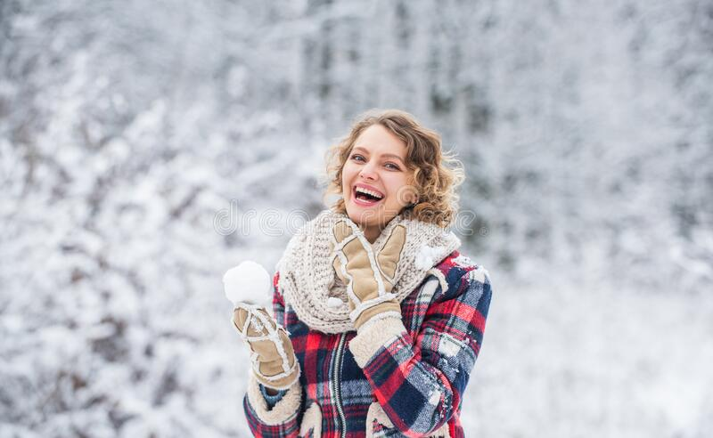 Look at this. girl make and play snowball. winter activity. happy woman enjoy winter landscape. woman warm clothes in royalty free stock image