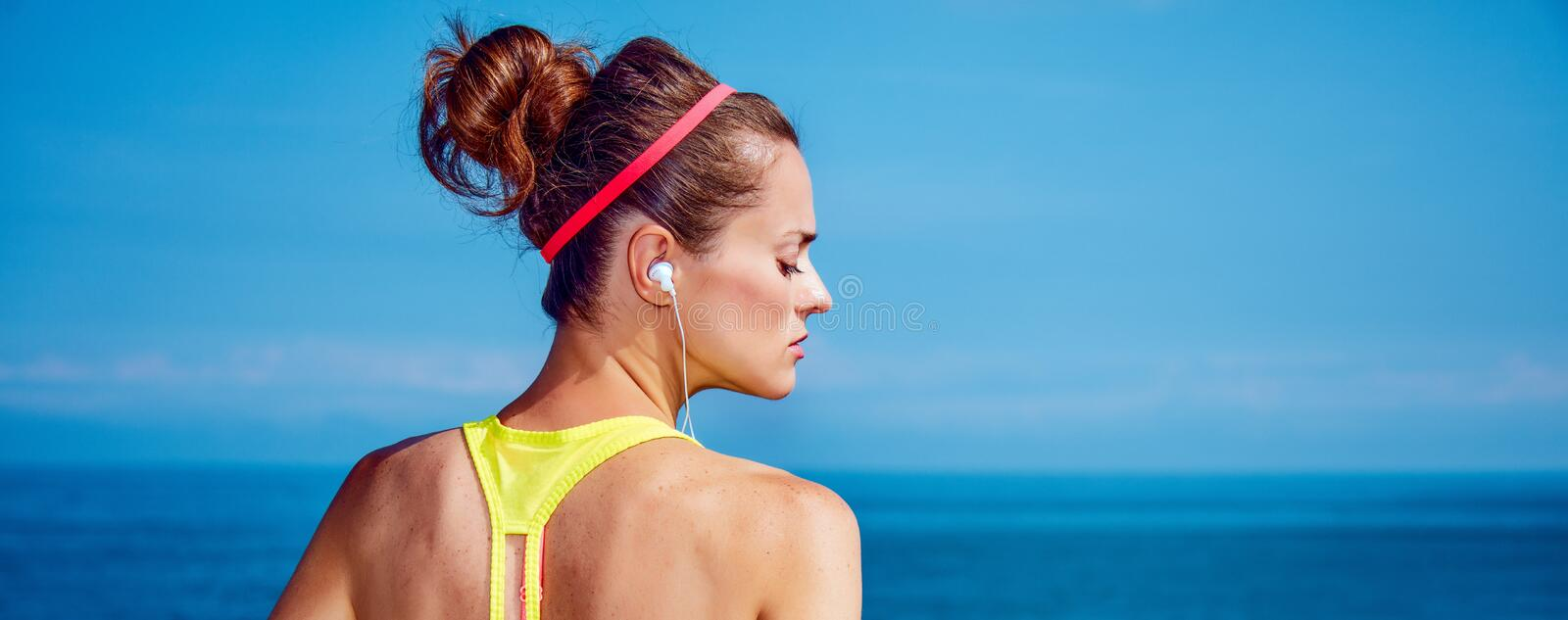 Relaxed fitness woman listening to music at embankment stock images