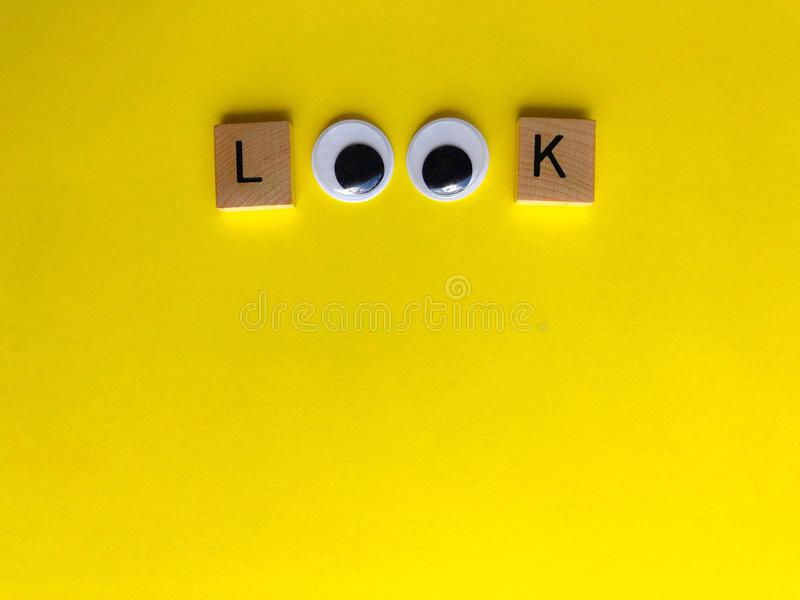 Look with googly eyes, Creative fun concept. Look in wooden letters , with googly eyes as the letter o`s, on a yellow background with copy space. Creative fun stock image
