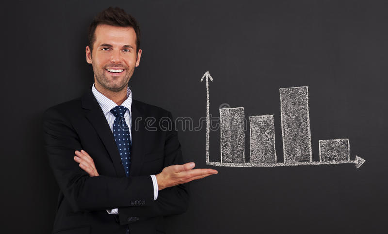 Look at this graph. Smiling businessman presenting graph on blackboard royalty free stock image