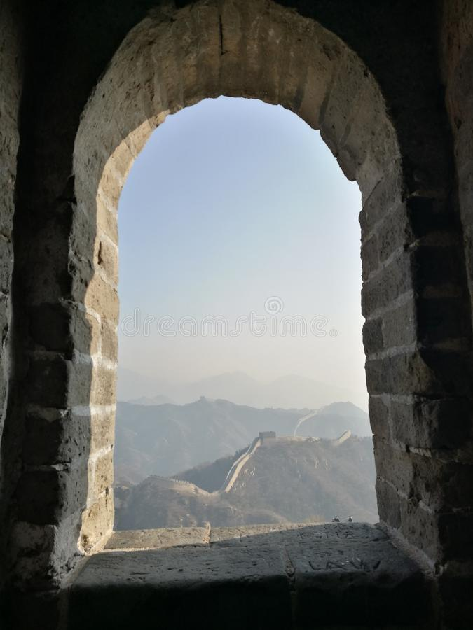 Look at the Great Wall through the window hole. Looking through the window hole to see the Great Wall and the mountains.Beijing Badaling Great Wall royalty free stock photo