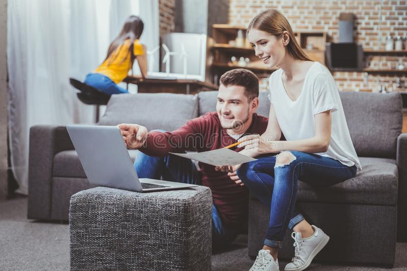 Concentrated blonde looking at computer. Look here. Handsome male person expressing positivity while consulting his colleague royalty free stock photos