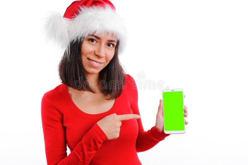 Look here my profile cool site link or app. Young woman in christmas red dress and Santa hat hold smartphone show royalty free stock photo