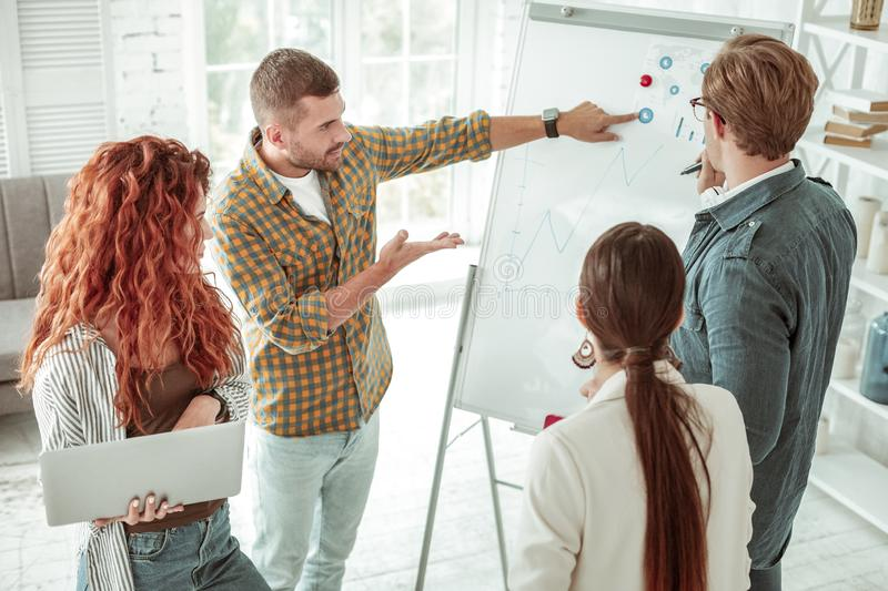 Serious young man pointing at the whiteboard royalty free stock photo