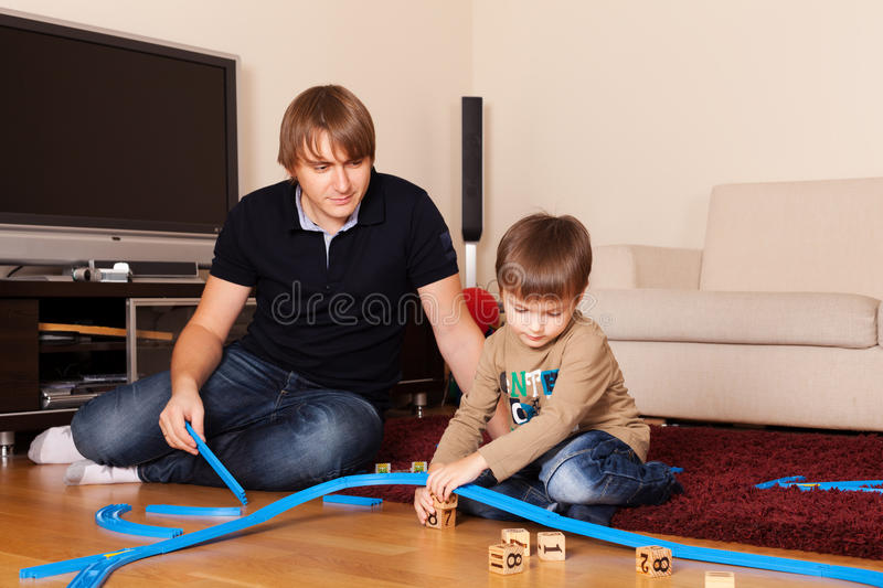 Look, how fast he is growing. Father is playing with son in toy railroad stock photos