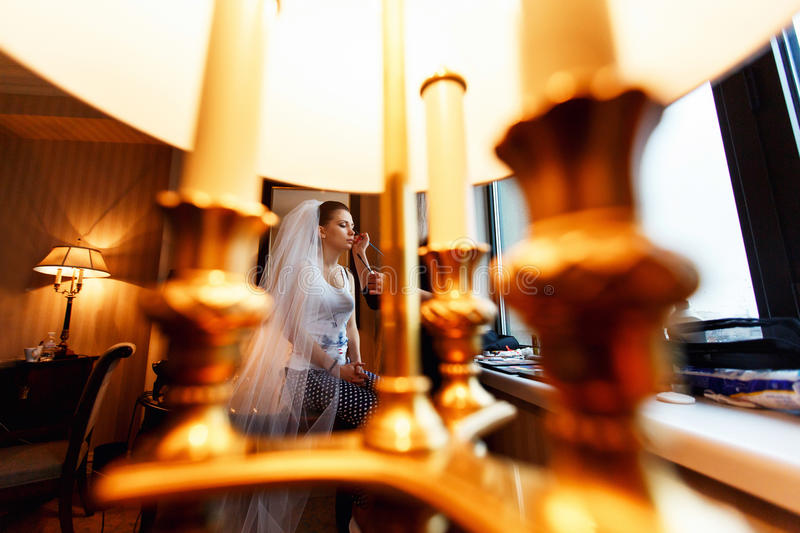 A look through a lamp on a bride while she does a make-up stock photos