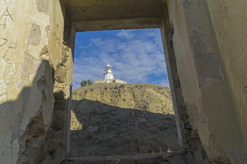 A look at the lighthouse from the window of a ruined house. View of the new lighthouse from the window of the old abandoned house. Crimea, Cape Meganom stock photo