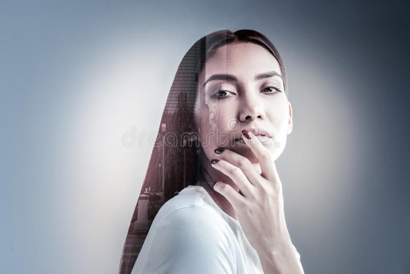 Portrait of attractive brunette that covering mouth. Look at me. Amazing model standing in semi position and touching lips while keeping silence in studio stock photography