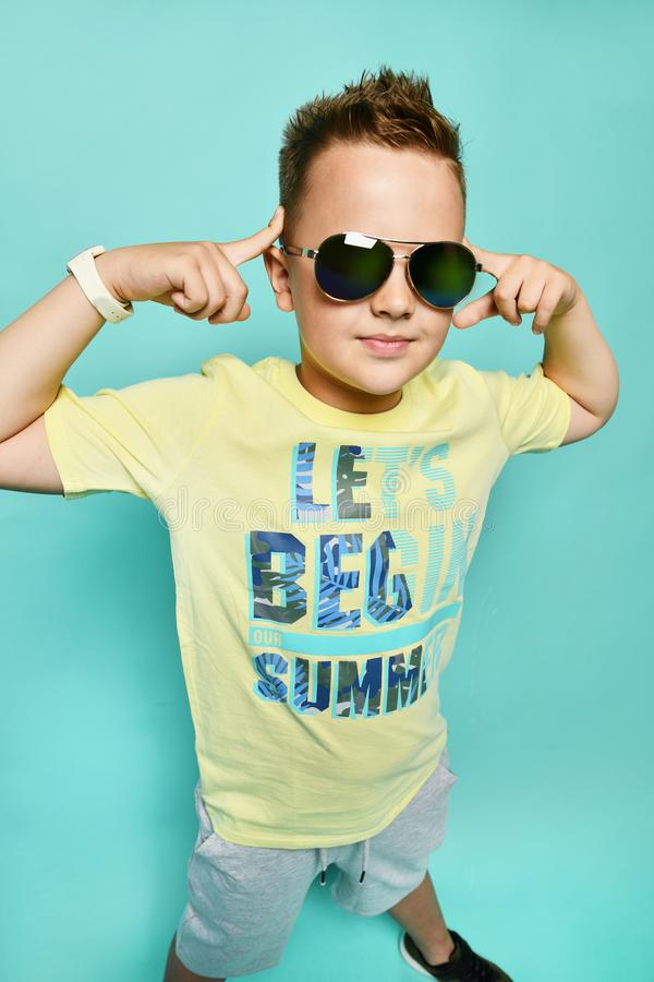 Look at me. Full length of cheerful young man adjusting eyewear and looking at camera while standing against blue background royalty free stock photo