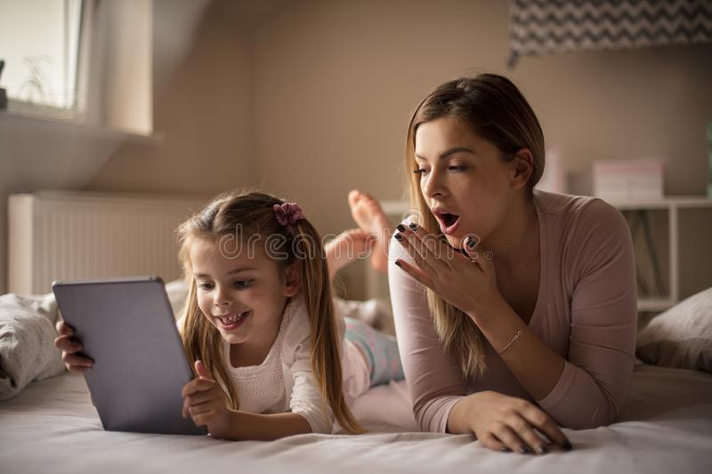 Look this mom. Mother and daughter using digital tablet royalty free stock photo