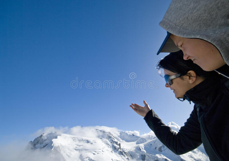 Look at Mont Blanc. Two tourists looking at Mont Blanc peak royalty free stock photo