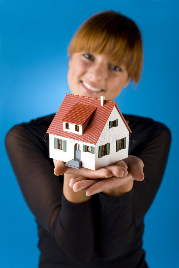 Look at my little house. Beautiful woman with house miniature in hands. Smiling and looking at camera. Blue background, front view. Focus on miniature royalty free stock photo