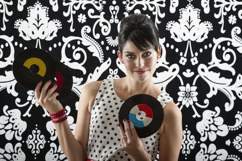 Look at my record. Young woman is stylist 60's inspired clothing, showing off three vinyl records royalty free stock photo