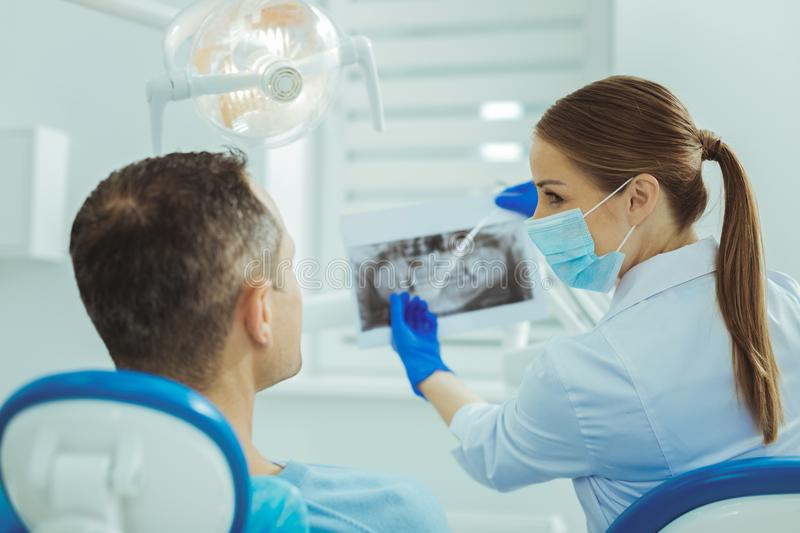 Charming assistant talking to her patient. Look at this. Professional stomatologist turning head while demonstrating x-ray picture stock image