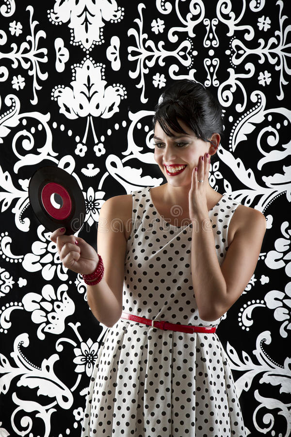 Look at that record. Young woman in front of a black and white textured background with 60's inspired style, holding a small record with a red label stock image
