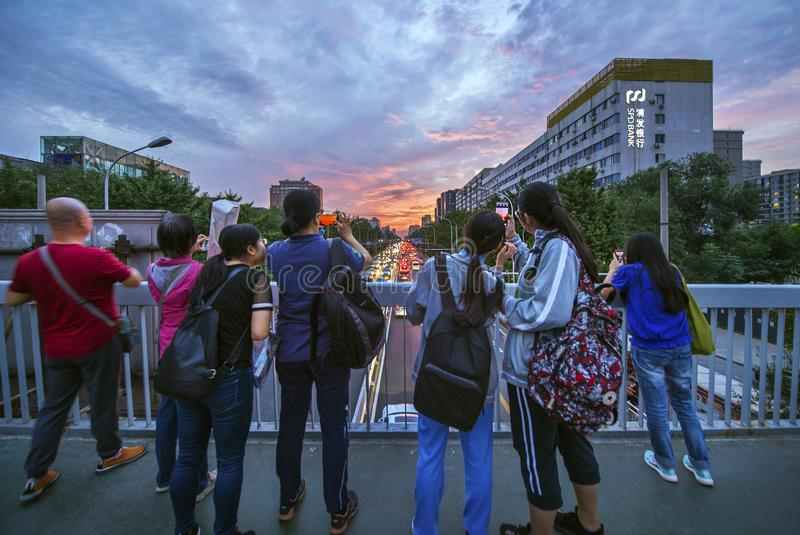 Look at the rosy clouds. N the evening of September 18, 2018, in Beijing, red clouds filled the sky, and citizens raised their cell phones to make beautiful stock images