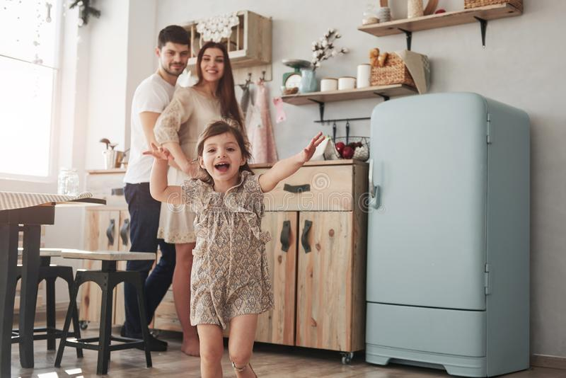 Look, it`s cameramen there. Playful female child have fun by running in the kitchen at daytime of front of her mother royalty free stock photos
