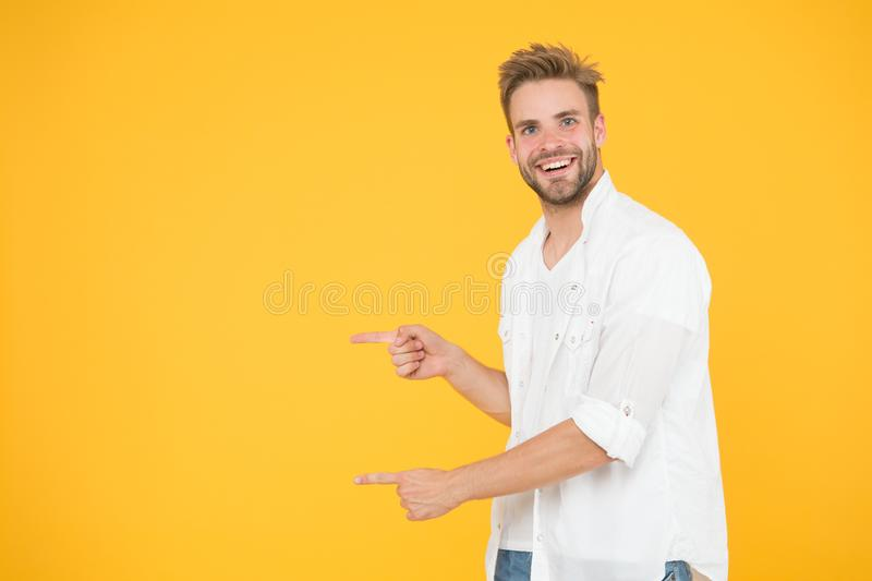 Look there. Man pointing at copy space. Check this out. Man muscular handsome smiling unshaven guy on yellow background stock image