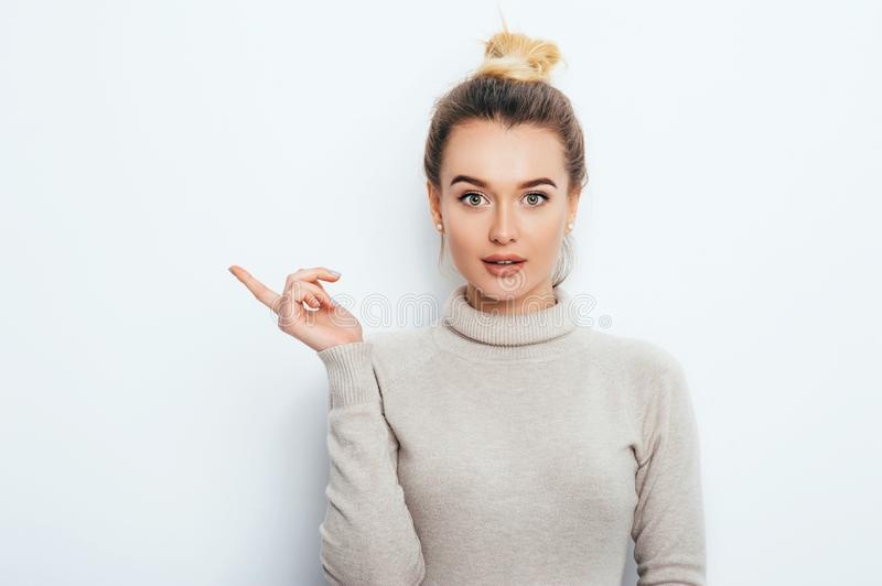 Look There! Surprised Attractive young female lady wearing in sweater with hair bun showing emotions on white wall. Shocked woman. Points with forefinger at stock photo