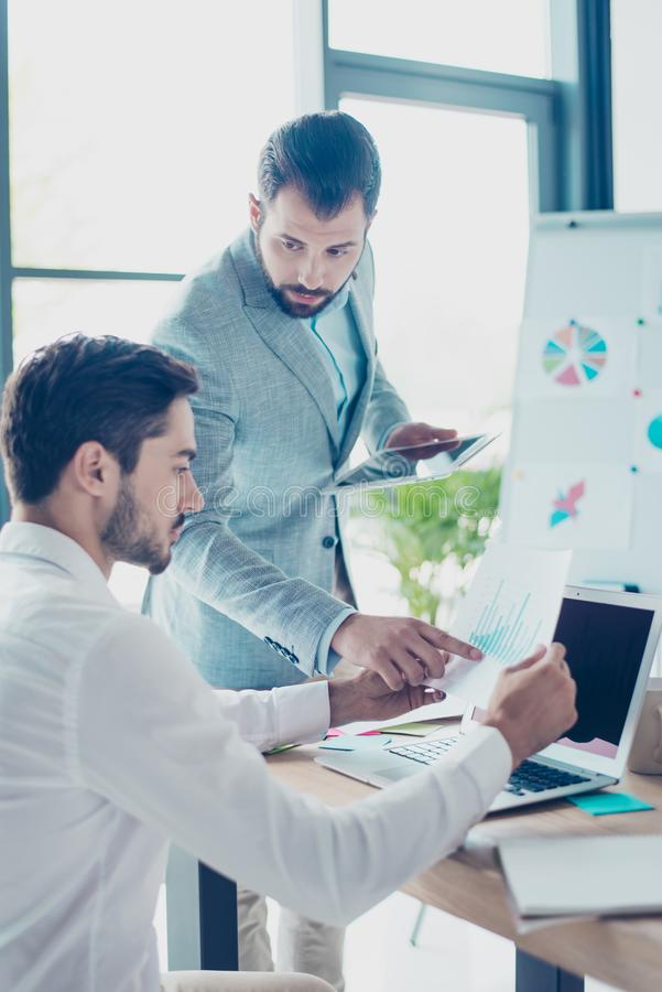 Look at this! Two male partners are discussing the data in report, sharing opinions and ideas, in light modern work station, wear stock photos