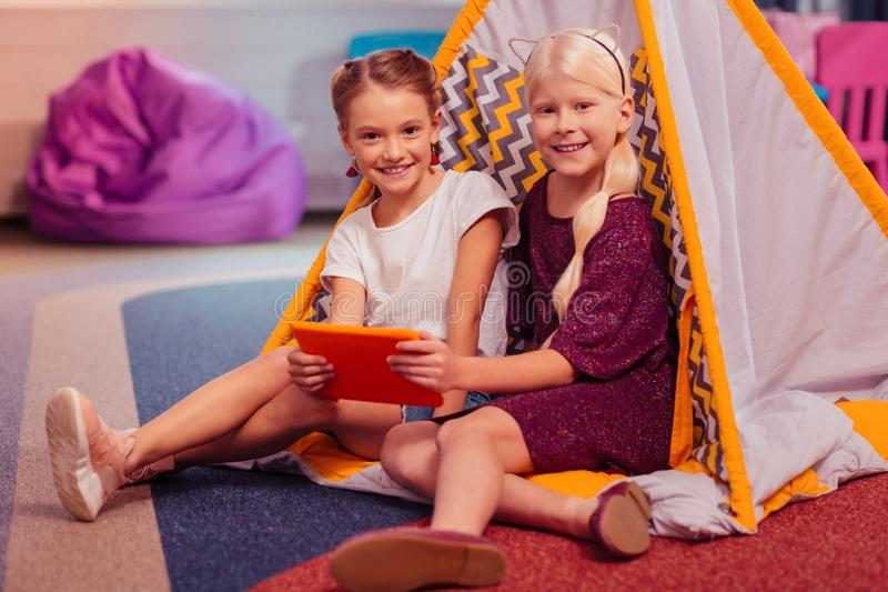 Delighted girls visiting birthday party of classmate. Look at us. Enigmatical girls expressing positivity while posing on camera royalty free stock photography