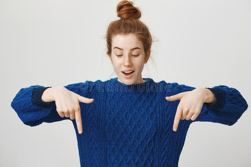 Look what we have there. Studio shot of curious good-looking red-haired female with freckles in bun and winter sweater stock images