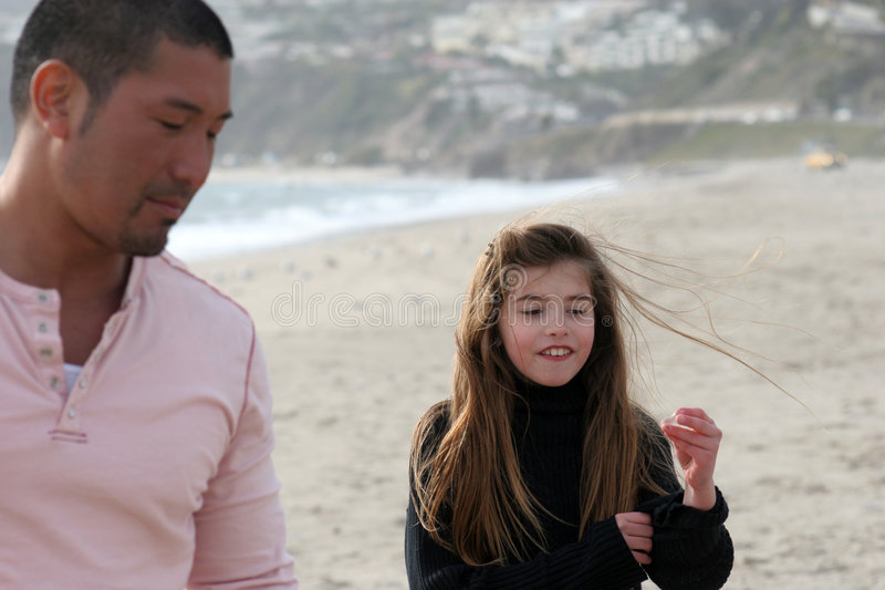 Look what I found. Child showing off seashell find to her Father (low depth of field) focus on child stock photography