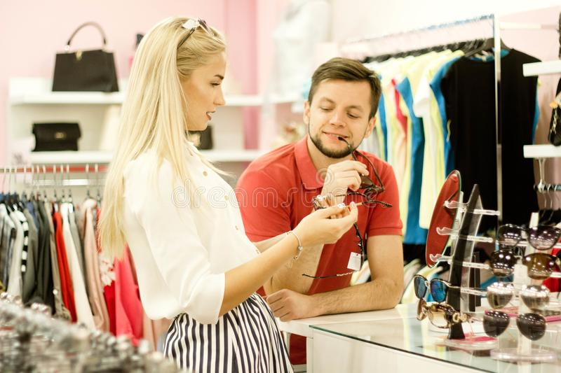 The guy and the girl in the store choose glasses, accessory royalty free stock photo