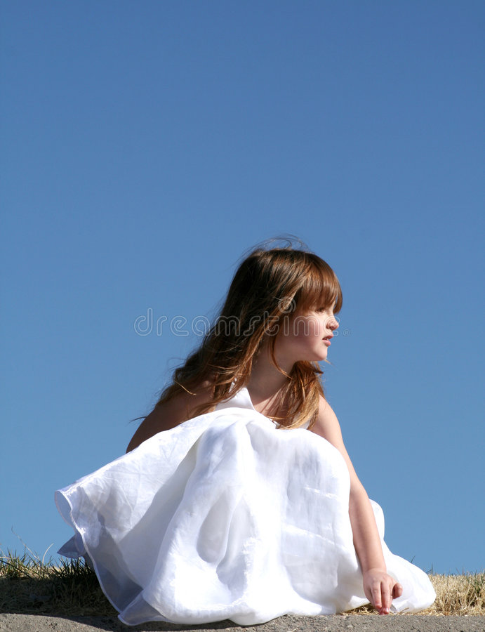 Looking. A little girl in a white dress against a blue background looking off into the distance stock photos