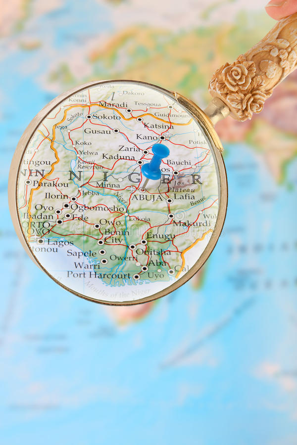 Looking in on Abuja, Nigeria, Africa. Blue tack on map of Africa with magnifying glass looking in on Abuja,Nigeria stock photo