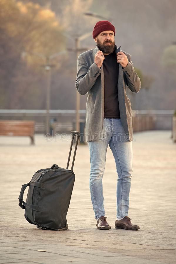 Looking for accommodation. Man bearded hipster travel with big luggage bag wait for taxi bring him to hotel. Travel tips. Traveler with suitcase arrive travel royalty free stock image