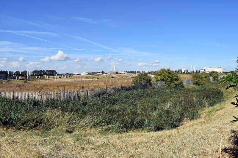 Old redundant factory area for reclamation. Looking across bushes and foliage to large area of where a factory once stood royalty free stock images