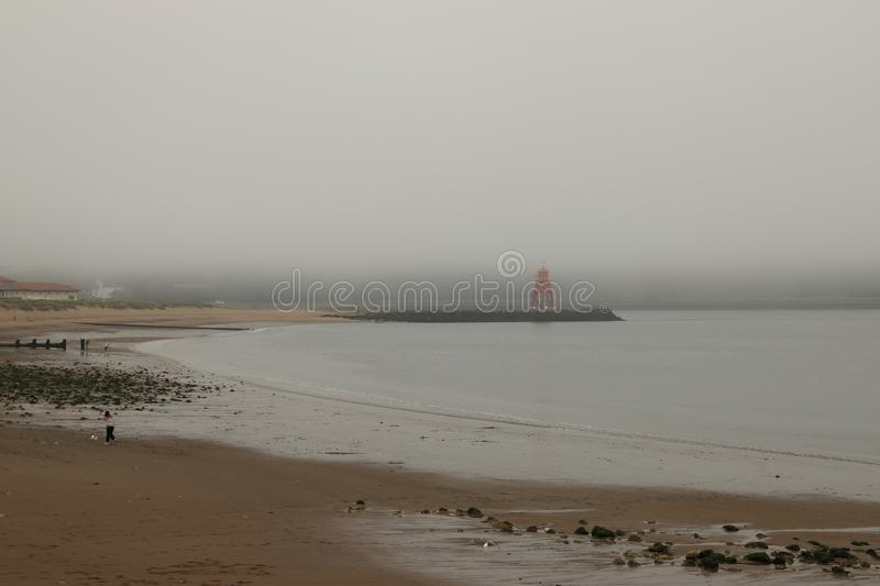Fog on the Tyne. Looking across South Shields beach at low tide towards a foggy River Tyne with the historic red Groyne lighthouse shrouded in fog and misty royalty free stock image
