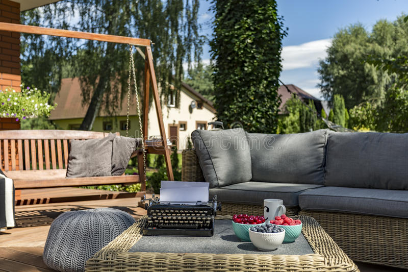 Looking for the afflatus. Veranda of a house with garden furniture, wooden swing and typewriter on a coffee table royalty free stock images