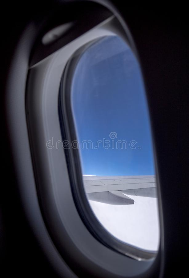 Looking at airplane wing through the window with blue sky during flight. stock photos