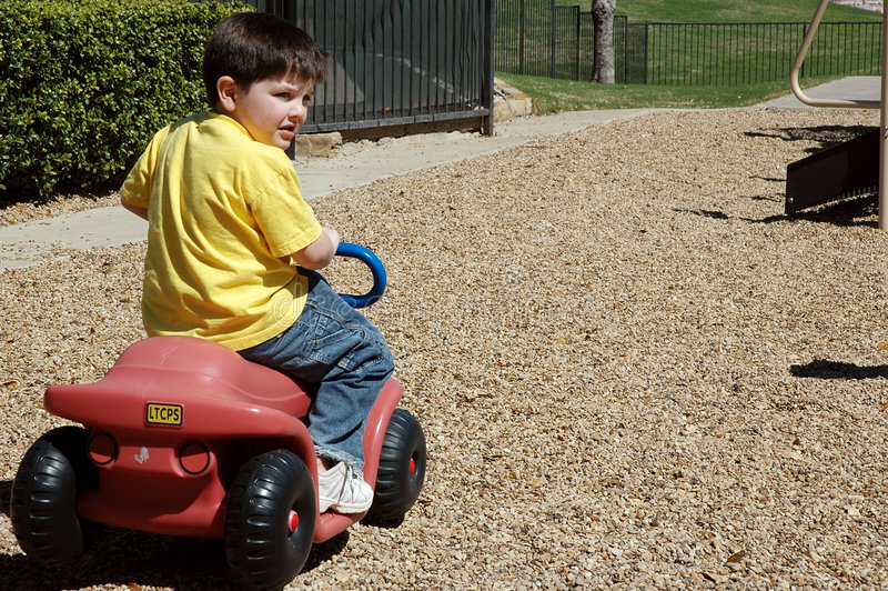 Looking Back. Little boy looks back as he rides a little car at the park. Space to the right for text or script stock photos
