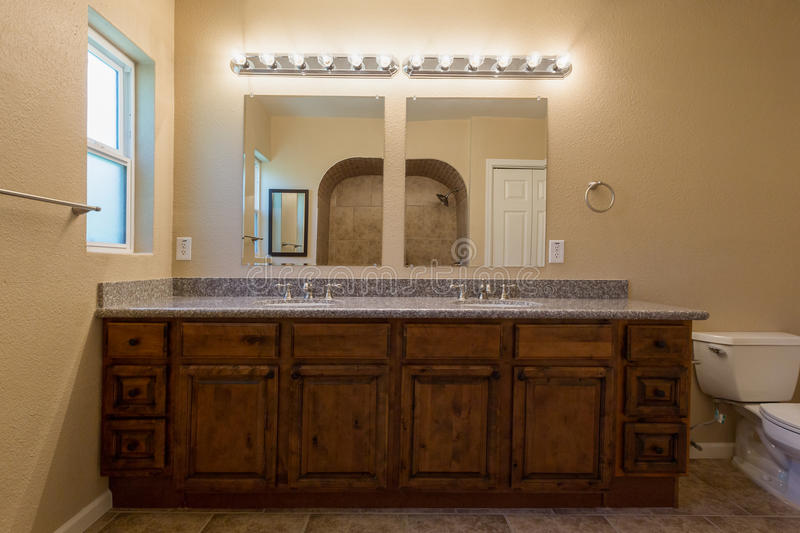 Looking Into Bathroom Mirrors. With full floor to ceiling view and cabinets. Main focusfrom countertop to above lights. A little soft on the cabinets royalty free stock photos